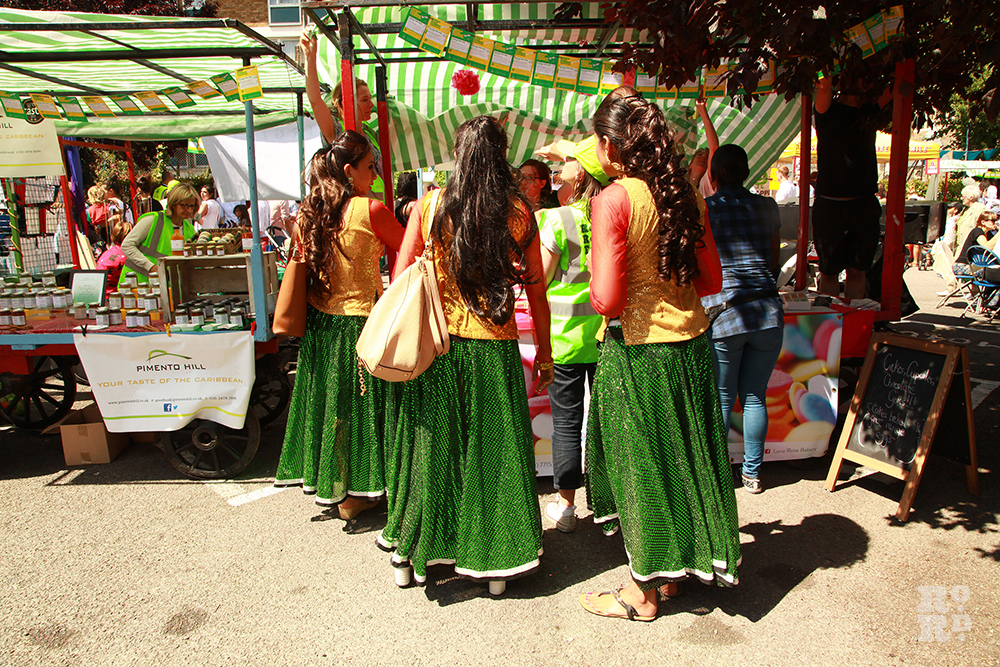 Bollywood dancers in green skirts and yellow tops at Roman Road Festival