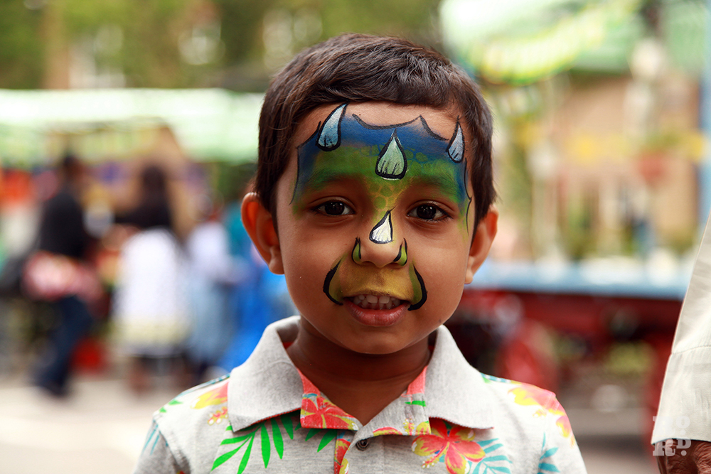 Asian boy with dinasaur face painting at Roman Road Festival