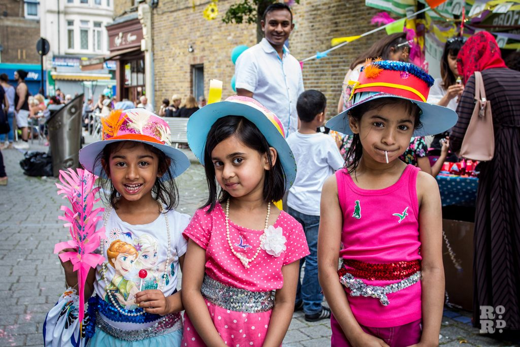 Three Asian girls wearing festival hats at Roman Road Summer Festival 2016