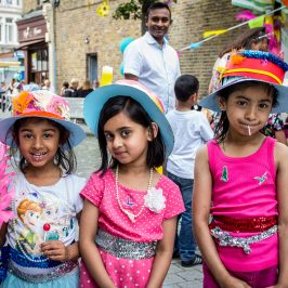 Three girls wearing Match Women hats made at the craft stall at Roman Road Festival 2016