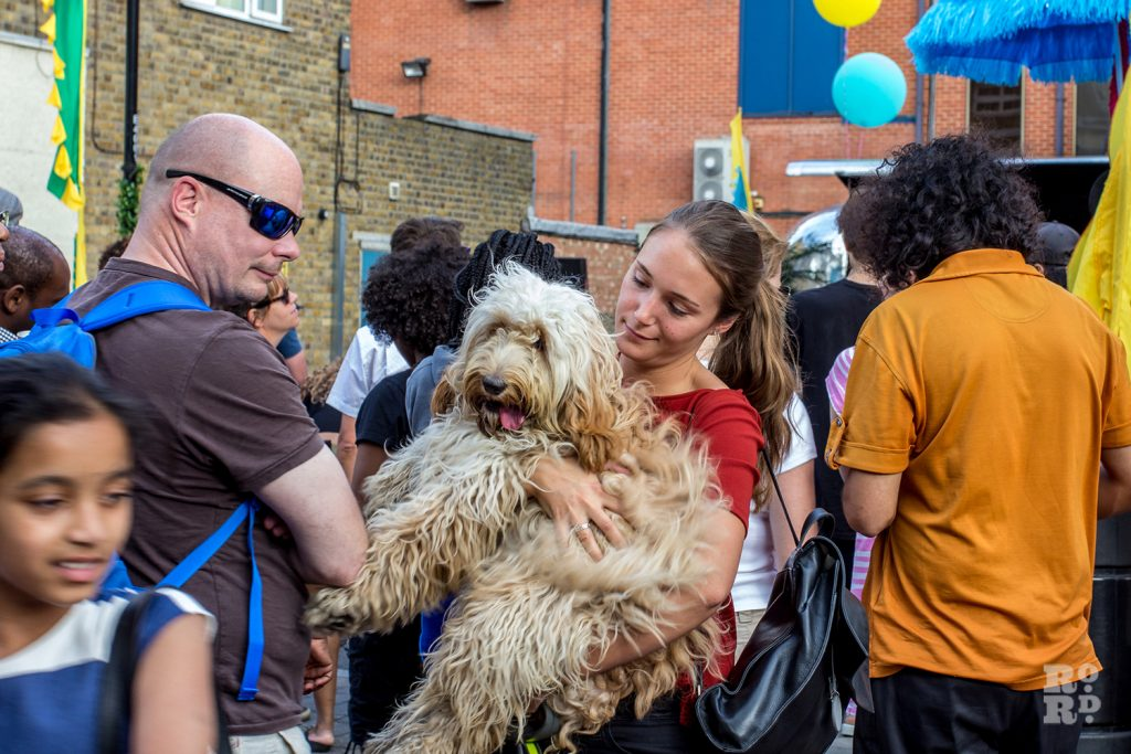 Woman holding large shaggy dog in her arms at Roman Road Summer Festival 2016