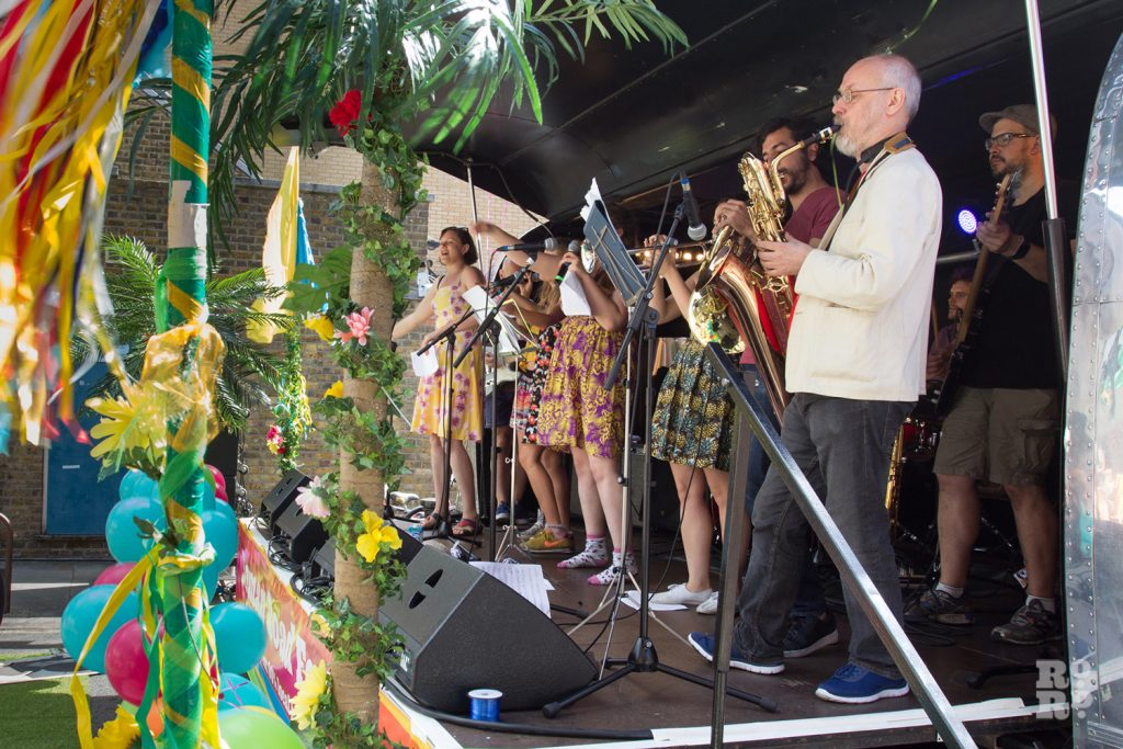Singers on the Airstream stage decorated with palm trees at Roman Road Summer Festival 2016