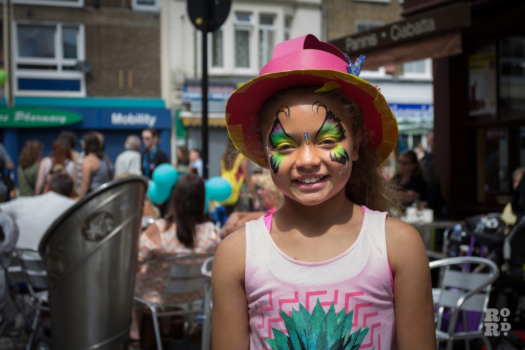 Young girl with face painted and wearing hand crafted Match Women's hat at Roman Road Summer Festival 2016