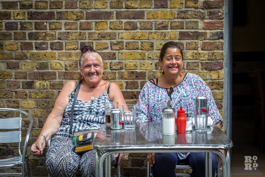 Two women sitting at a cafe table against a London brick wall at Roman Road Festival 2016