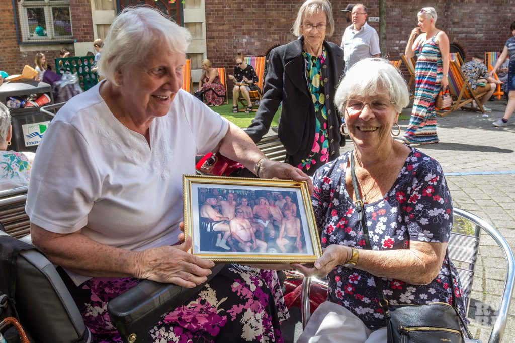 Two older women holding a framed print of the Bow Geezers nude calendar photo shoot at Roman Road Summer Festival