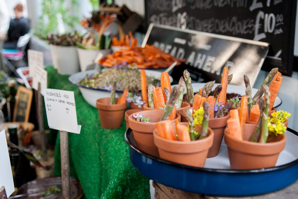 organic carrots and asparagus in mini terracotta flower pots