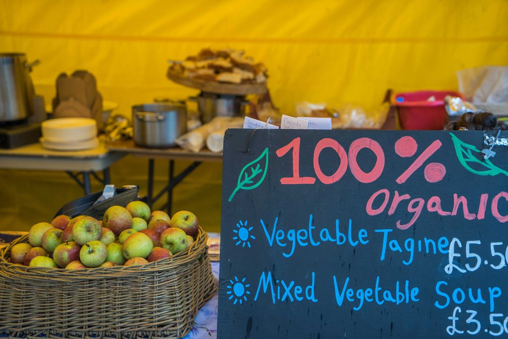 organic apples in a basket and blackboard sign with 100% orgnaic vegetable tagine and mixed vegetable soup