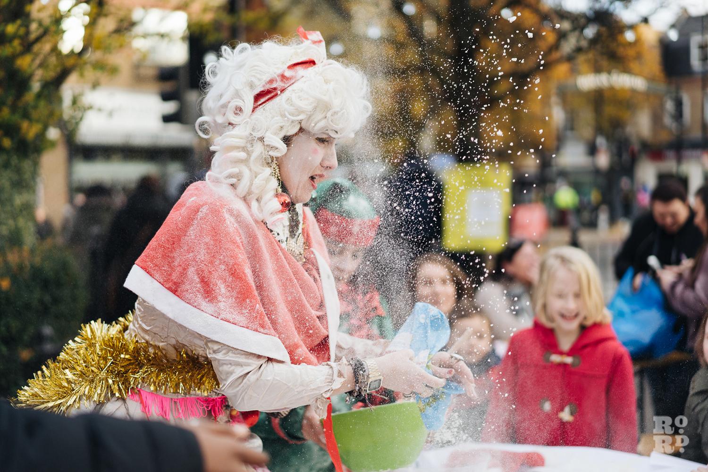 A festive character throwing flour into the air to entertain children at Roman Road Christmas Fair 2016 © Roman Koblov
