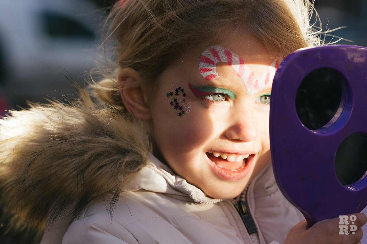 Girl looking in mirror at her face paint at Roman Road Christmas Fair 2016 © Roman Koblov