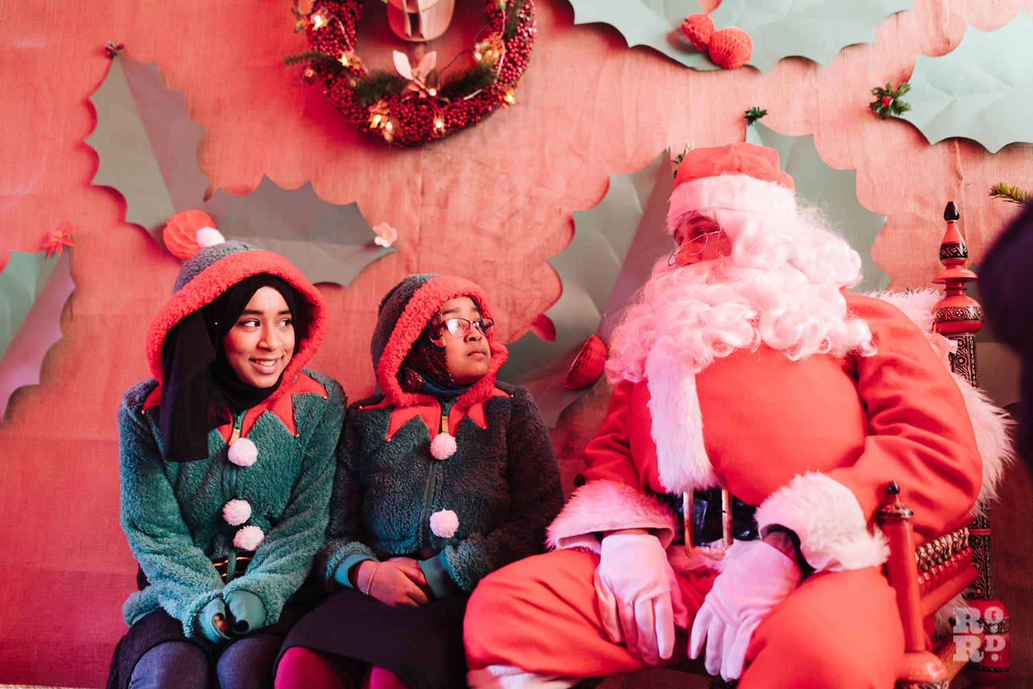 Santa sitting in grotto with two elves at Roman Road Christmas Fair 2016 © Roman Koblov