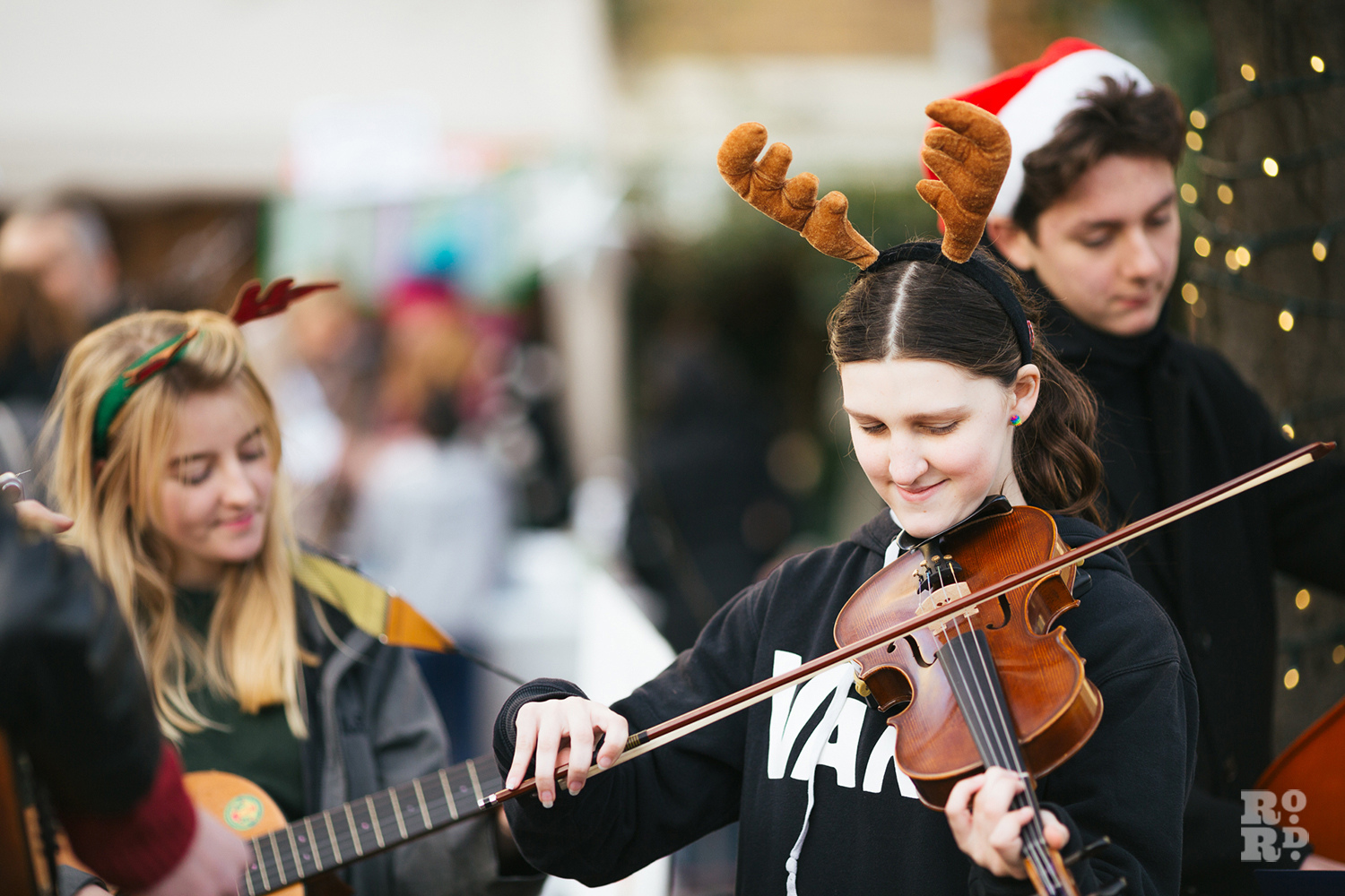 Young woman playing violin and wearing antlers at Roman Road Christmas Fair 2016