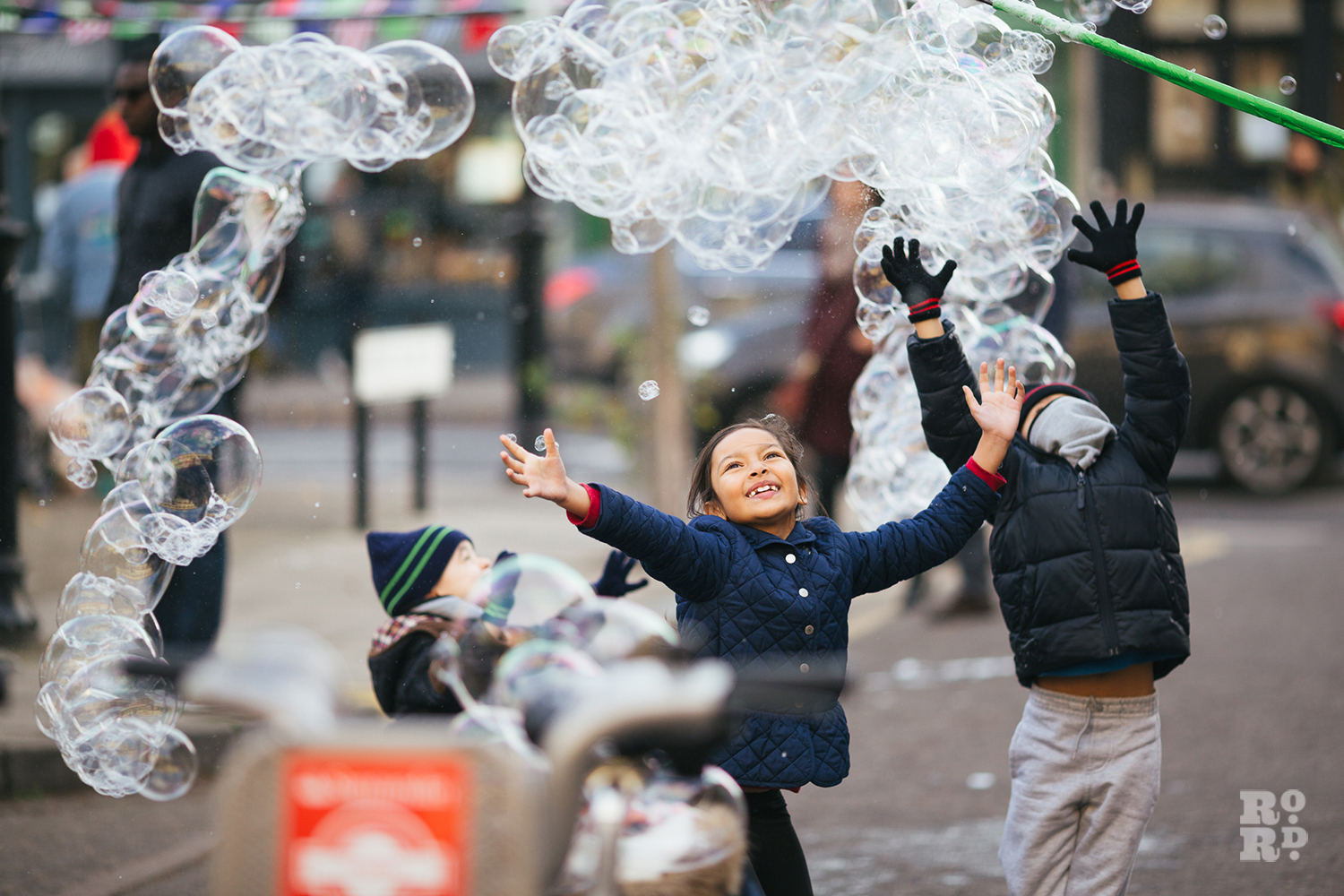 Child reaching up to giant bubbles at Roman Road Christmas Fair 2016