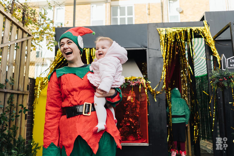 Elf holding baby at Roman Road Christmas Fair 2016 © Roman Koblov