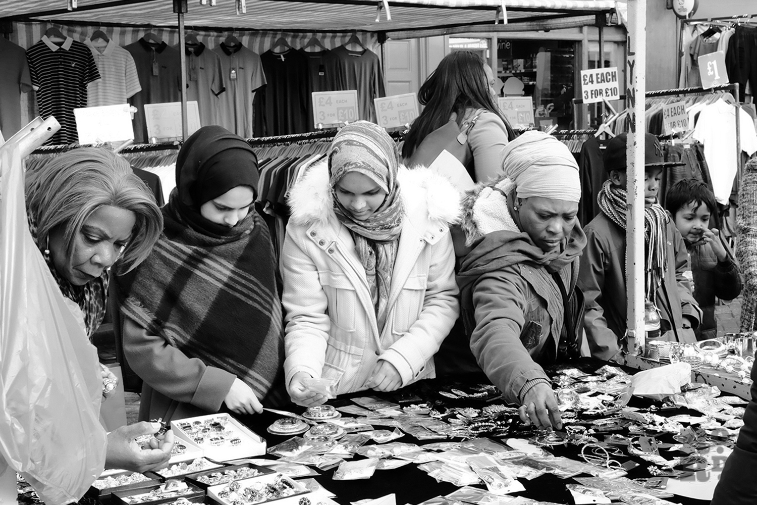 Roman Road Market stall selling jewellery with Aisan and black Afro-Caribbean women shopping, black and white photography