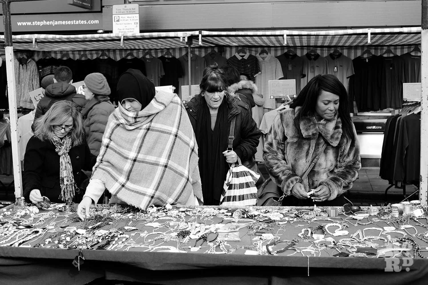 Roman Road Market stall selling jewellery with Asian and Black Afro-Caribbean women shoppers