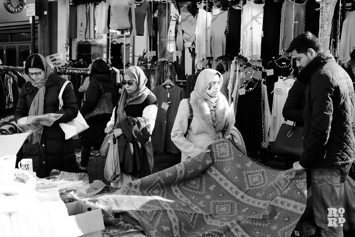 Roman Road Market stall selling rugs and homeware with Asian woman shoppers