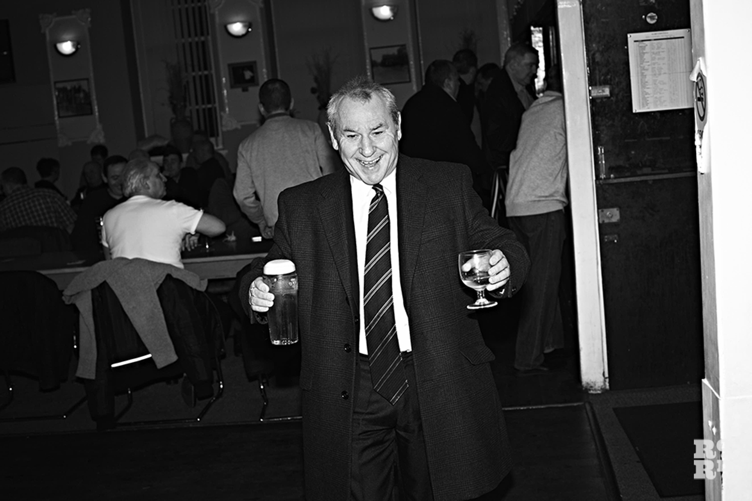 Man in suit carrying two drinks in the Globe Town Social club, East London, black and white photography