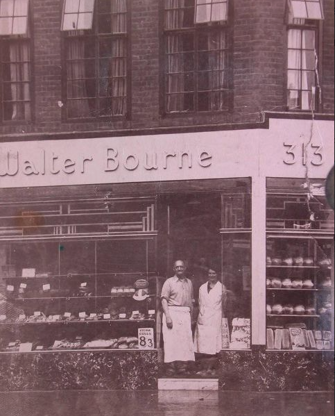 Black and white photograph of two bakers stood outside their bakery on Roman Road.