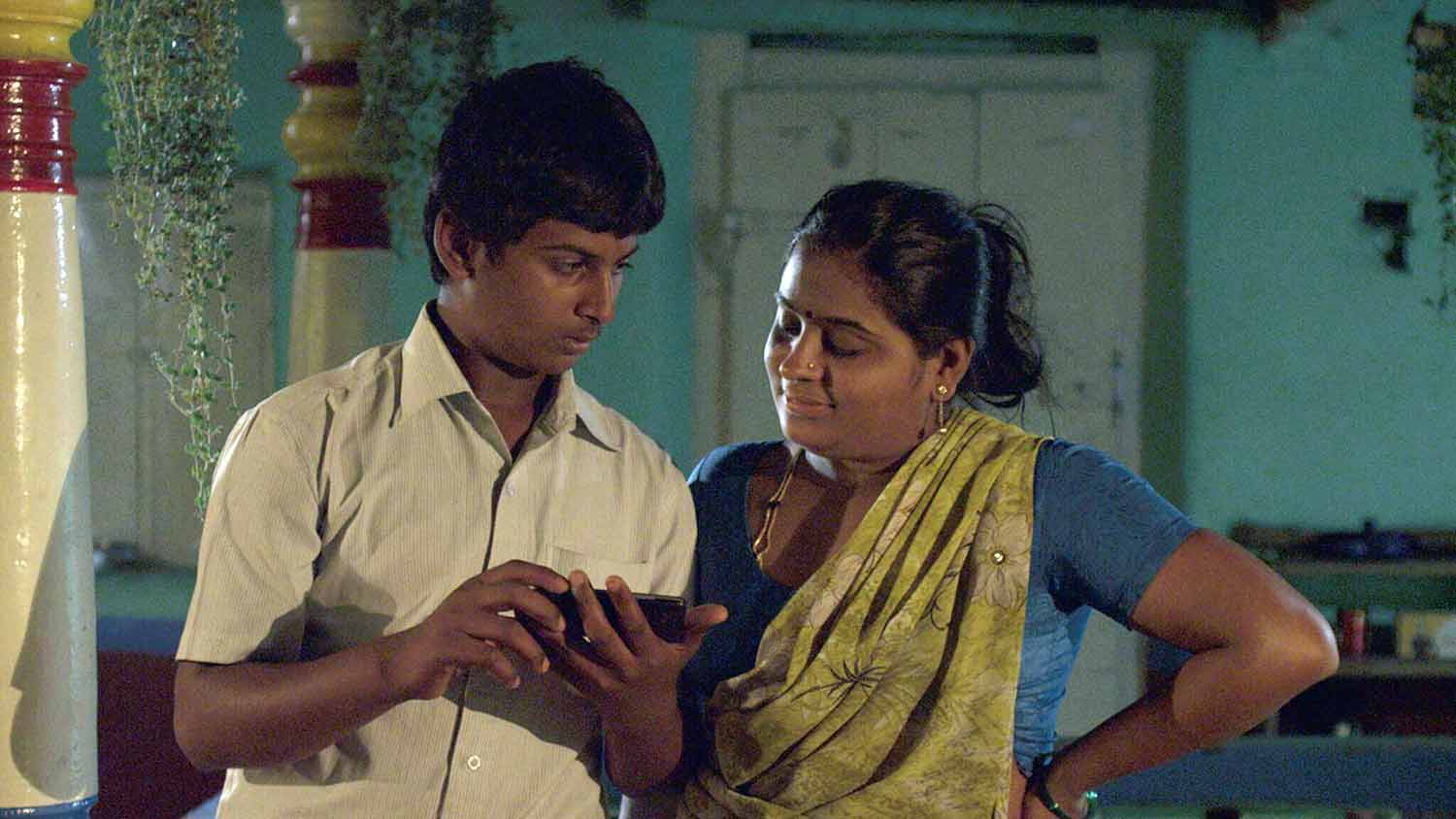 Scene from the film Balekempa in which a boy shows a girl something on his phone and watches for her reaction, shown at the East End Film Festival