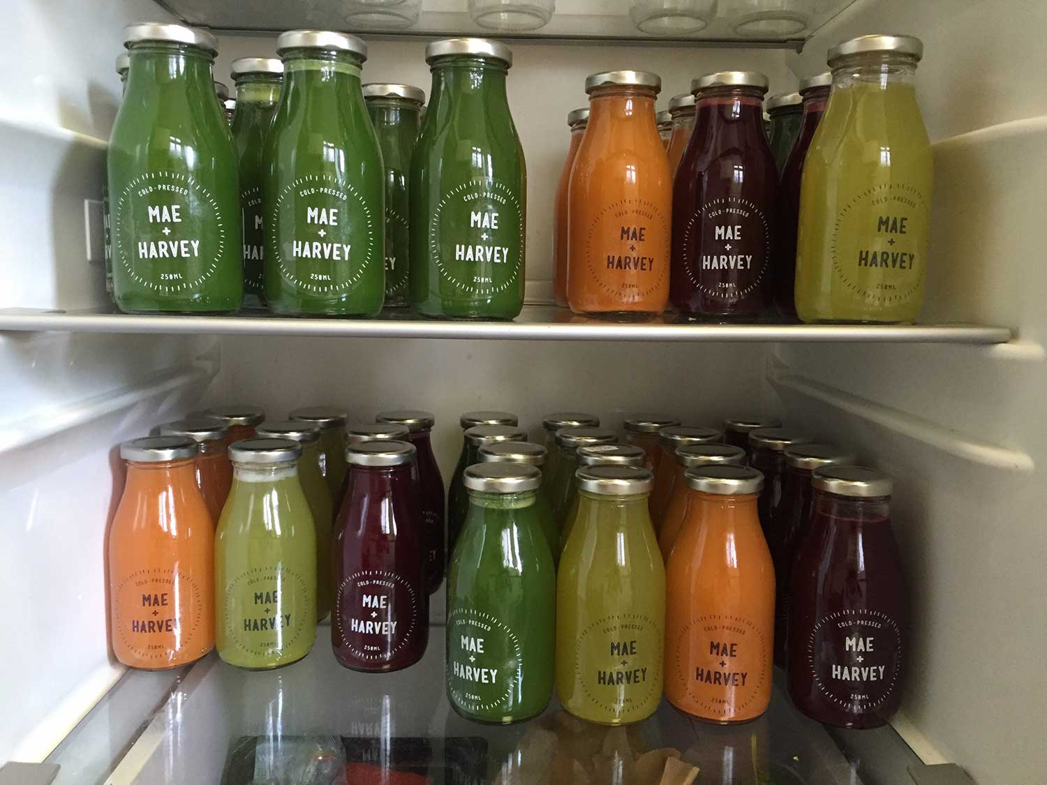 Various bottles of coloured smoothies in the fridge at Mae + Harvey, a cafe on Roman Road, in East London