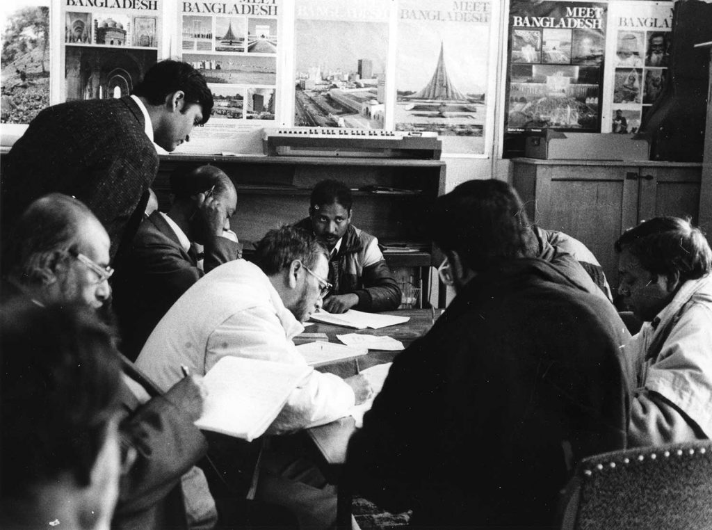 Black and white photograph of meeting of Bangladeshi community leaders at Toynbee Hall in the 1980s