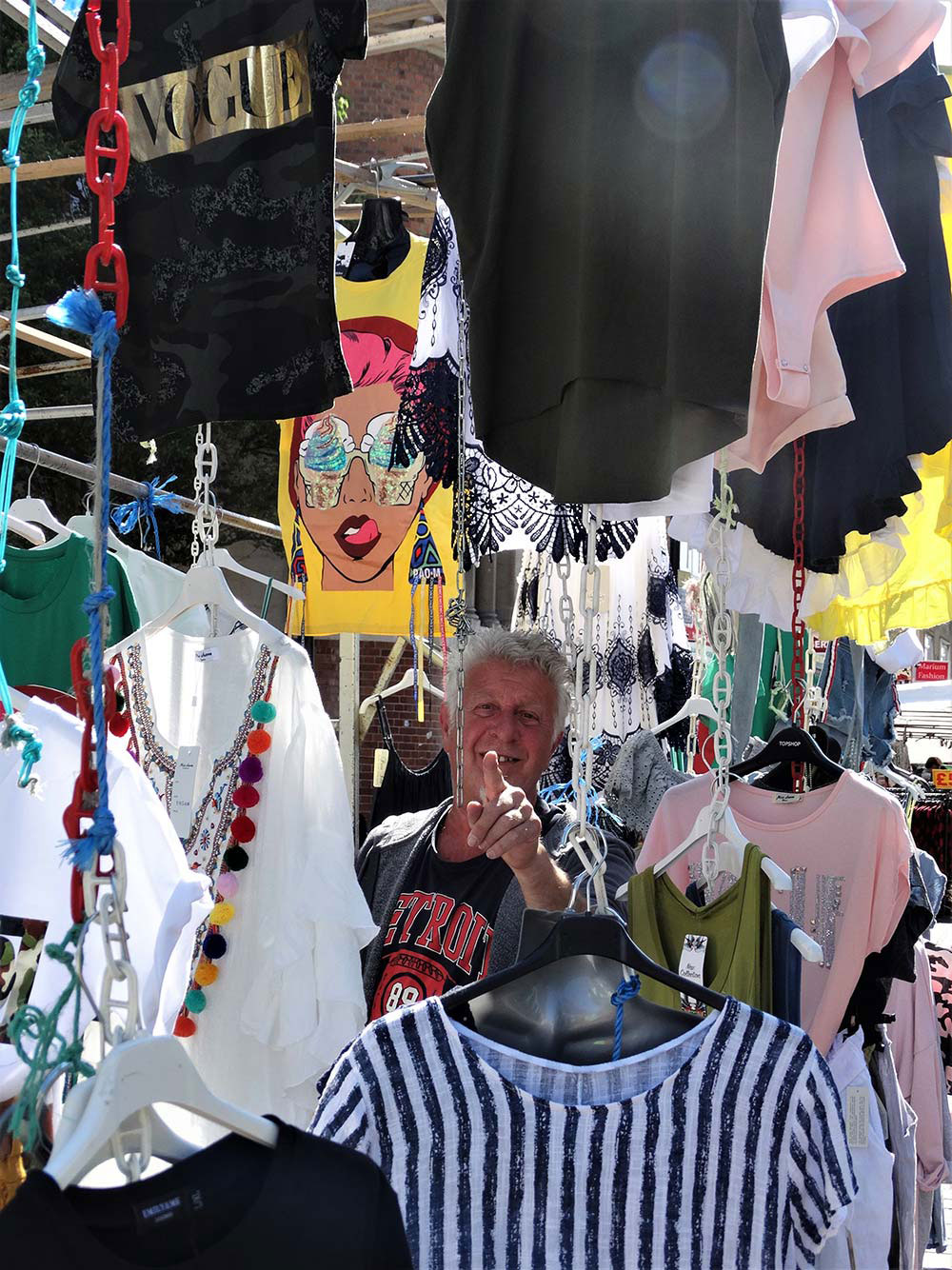 Market trader points through the clothes on Roman Road Market