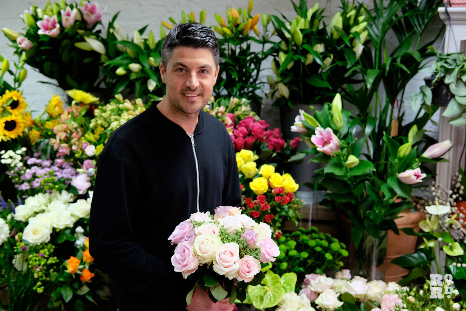 Male florist holding a bouquet of flowers in Denningtons florist, Roman Road, East London