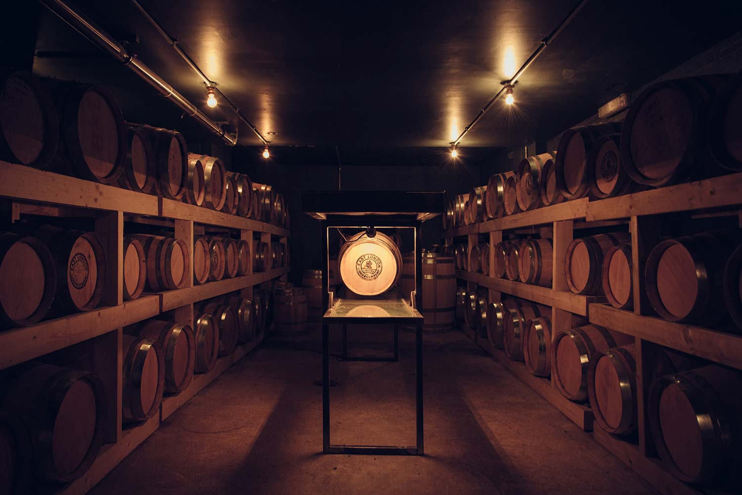 two rows of three layers of barrels with one barrel lit in the centre at the East London Liquor Company