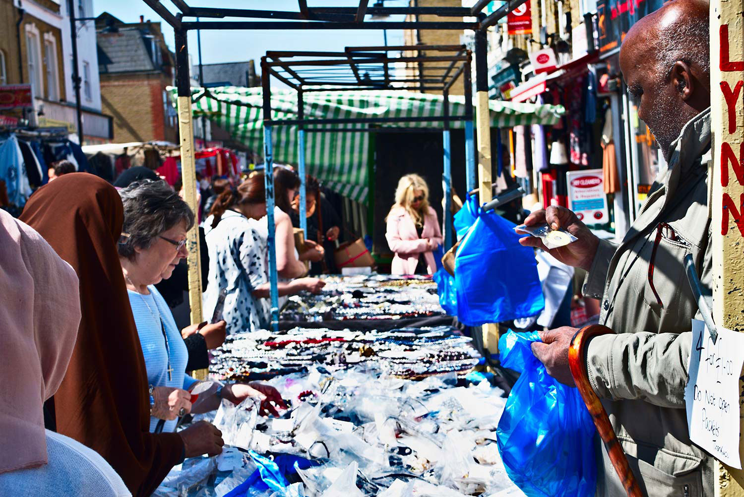 Shoppers buy jewellery at roman road market