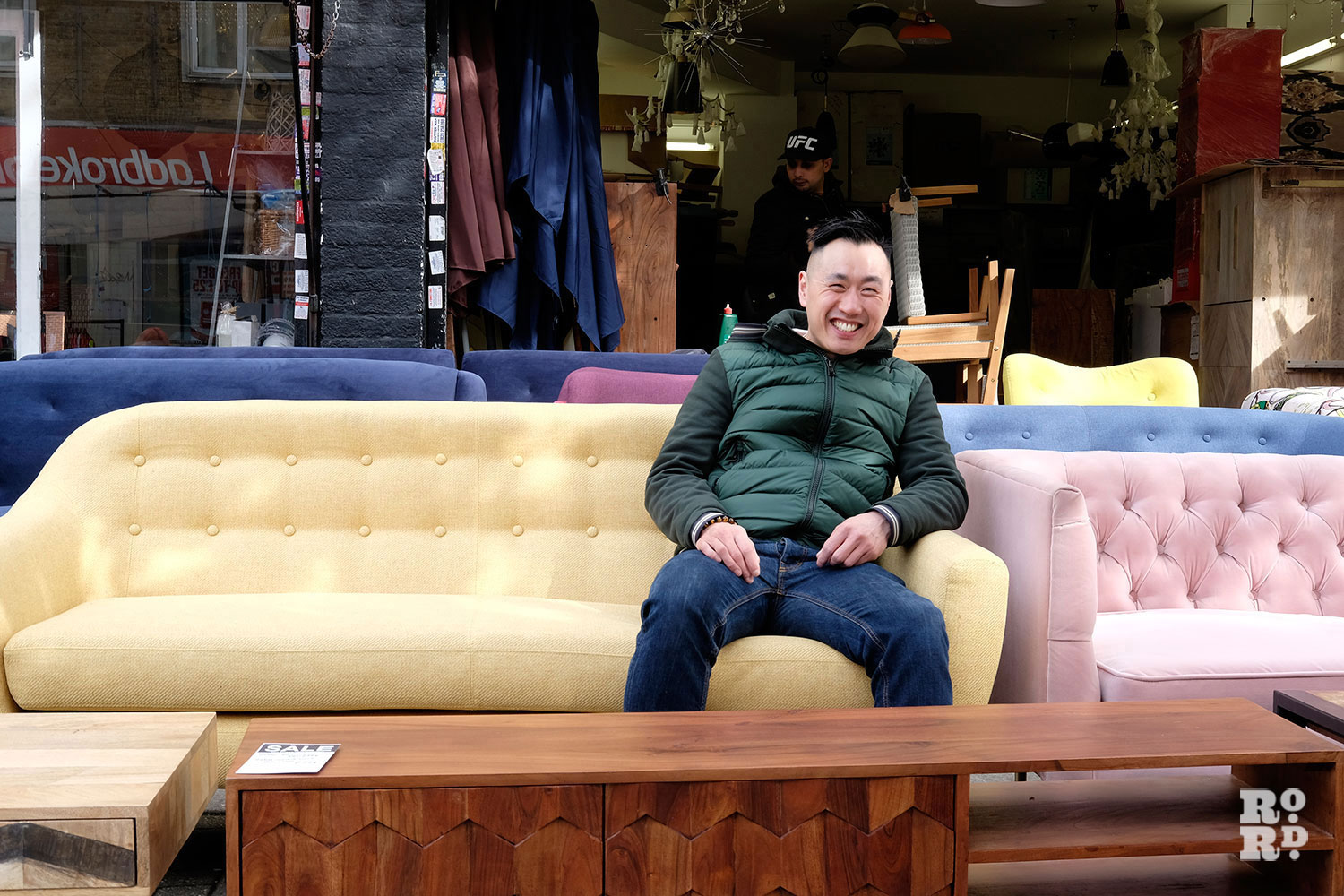 Shop owner sat on a yellow sofa he's selling outside his shop on Roman Road Market