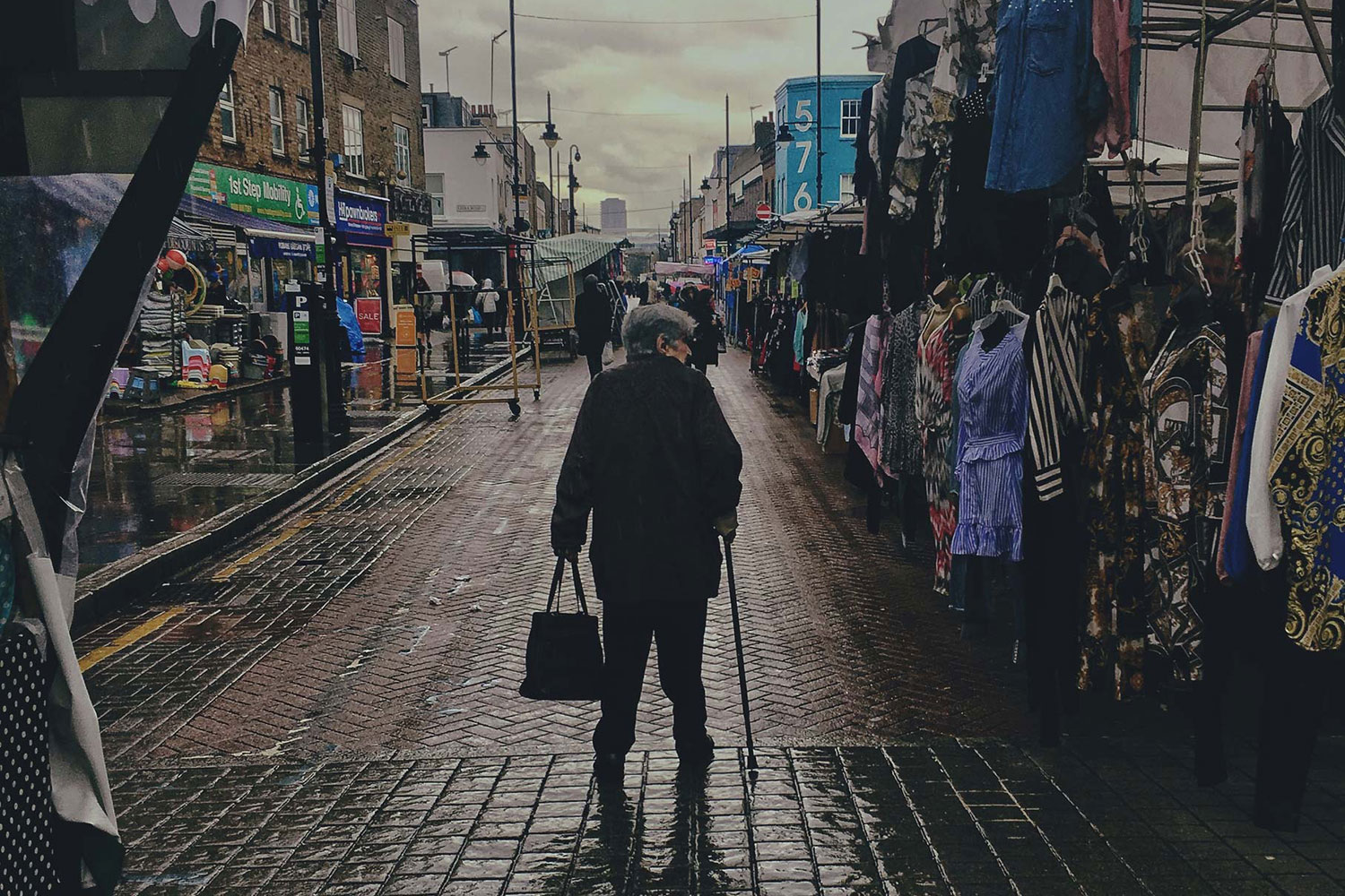 Woman walks down Roman Road Market, East London