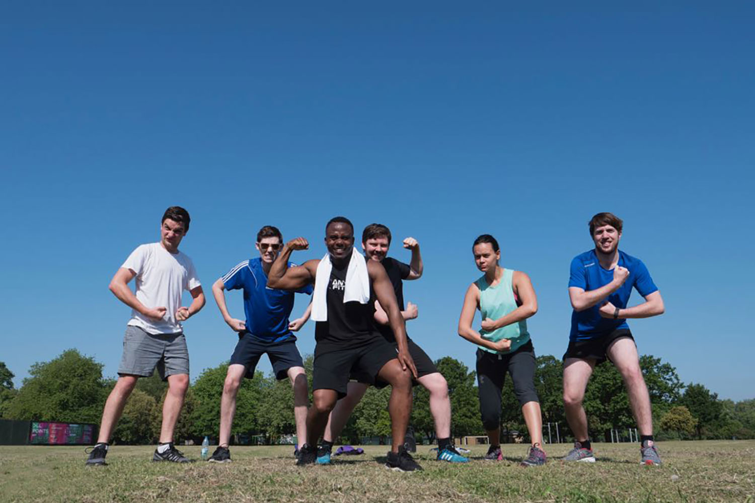 Participants of Victoria Park bootcamp posing to show their strength