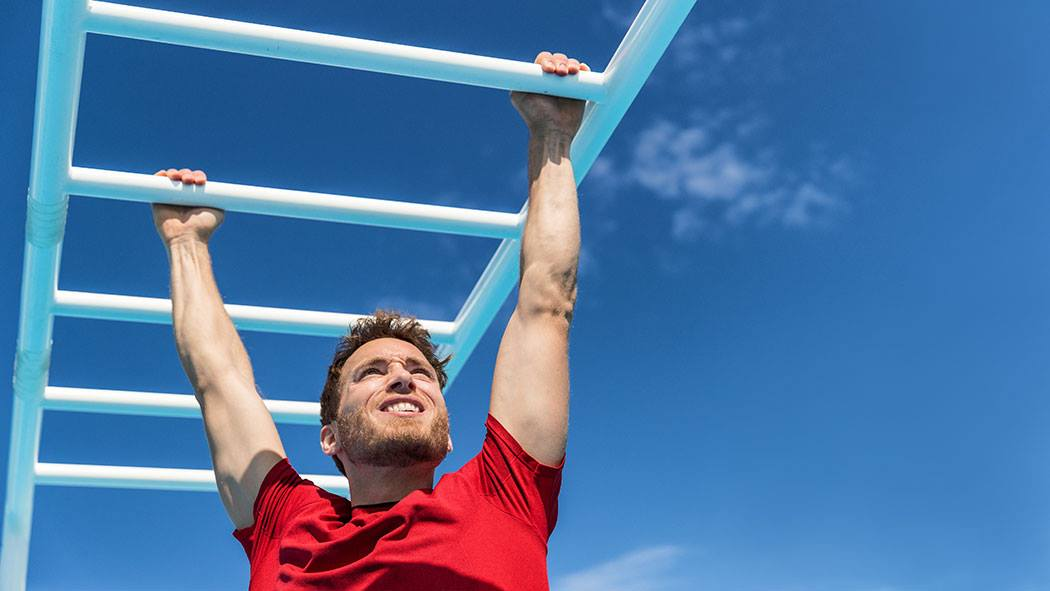 Man doing monkey bars at Anytime Fitness Bow Competition
