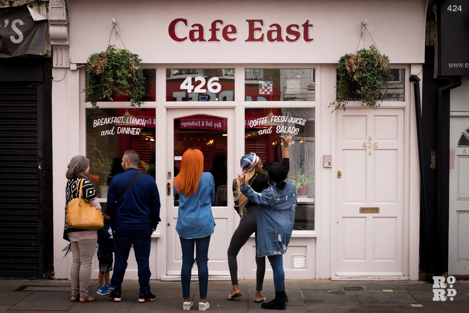 People outside cafe east roman road london