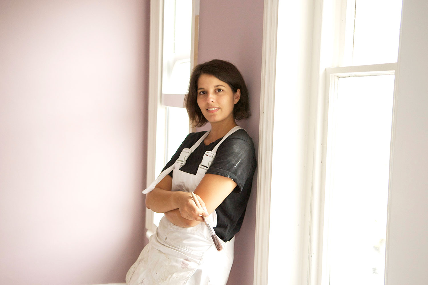 Jo Beharia, DIY Queen, in white overalls and holding a paintbrush