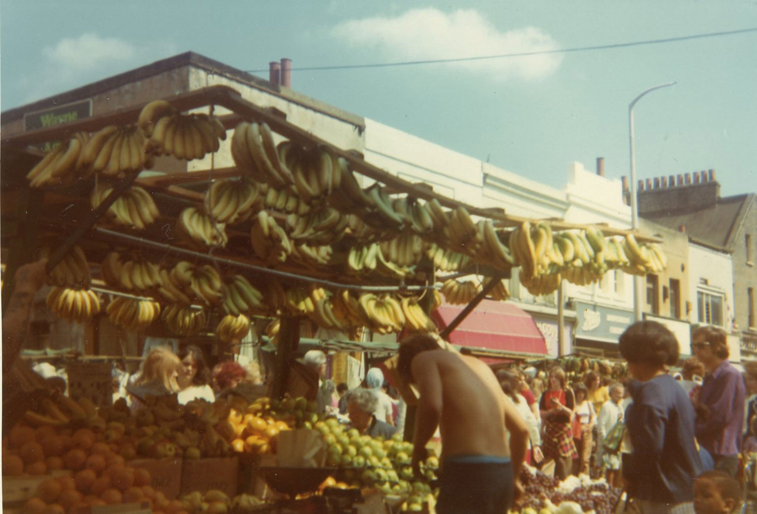 Archive image of shirtless market seller at his fruit stall on Roman Road, Bow, 1990s
