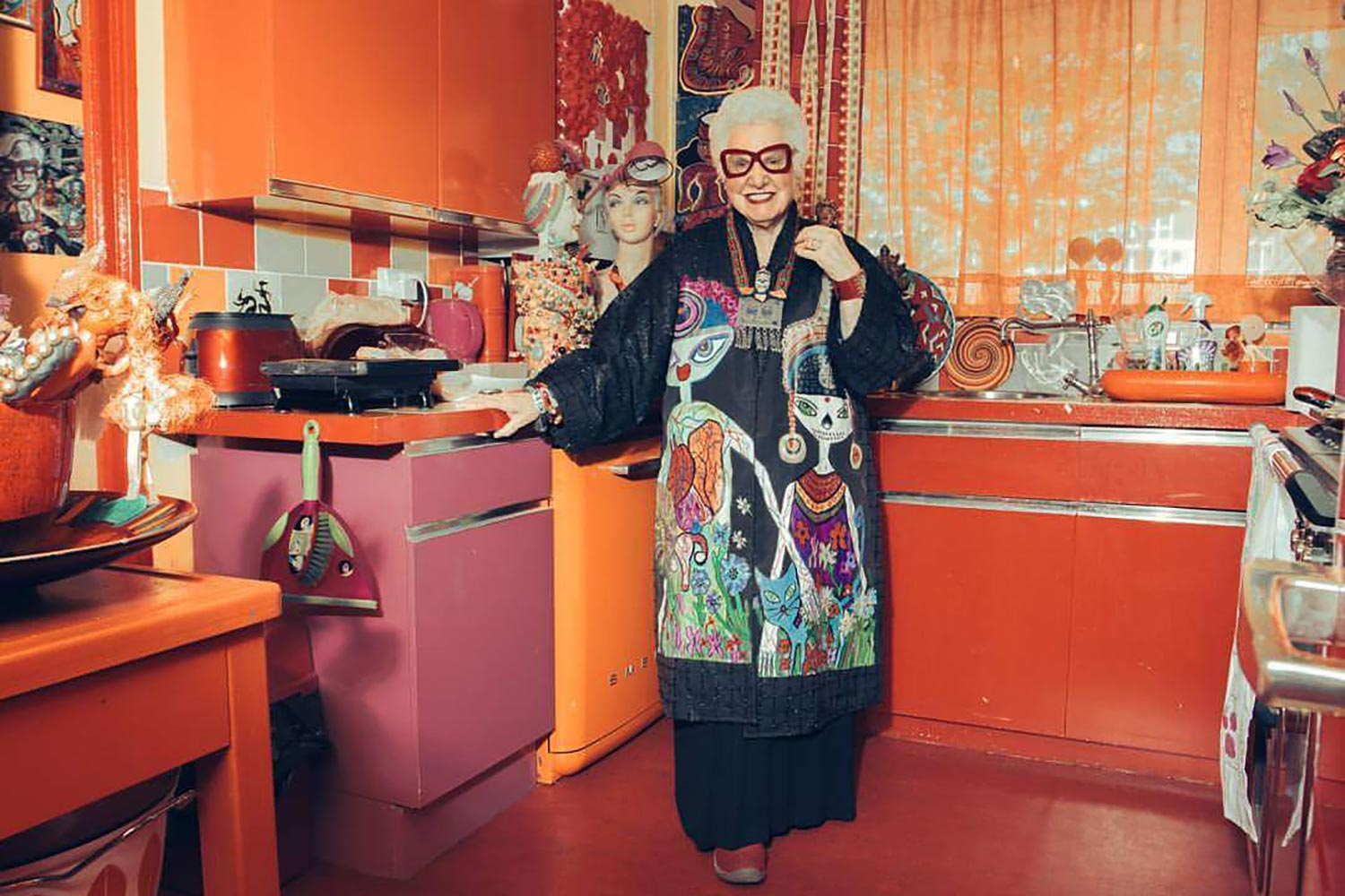 Sue Kreitzman standing in colourful 50s style kitchen of her home in Bow, East London
