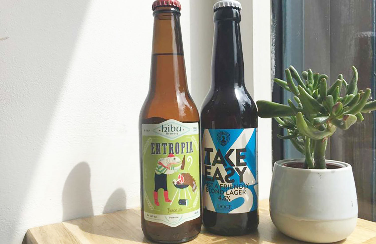 A bottle of Entropia blonde Ale and a bottle of Take Easy Blond lager next to a potted succulent at Symposium on Roman Road, in East London