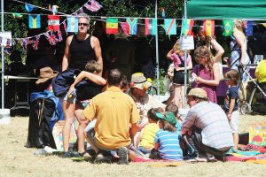 People sit for face painting at Tower Hamlets Cemetery Park Summer Fair