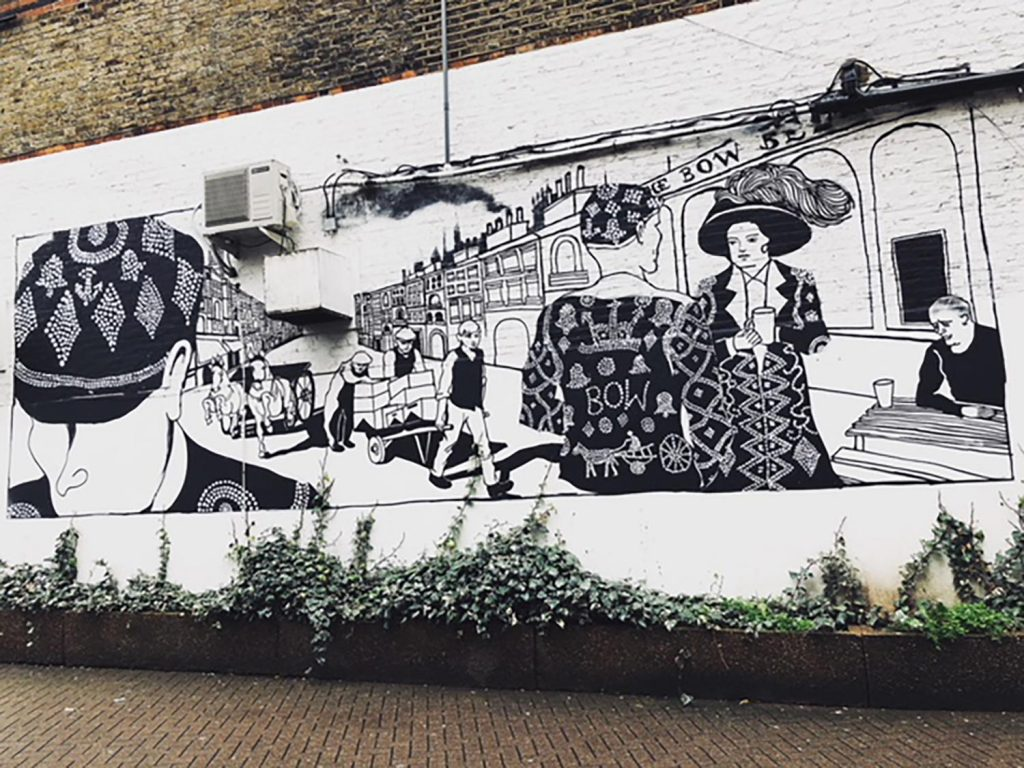 Black and white mural of pearly kings and queens on a wall near Bow Bells, East London