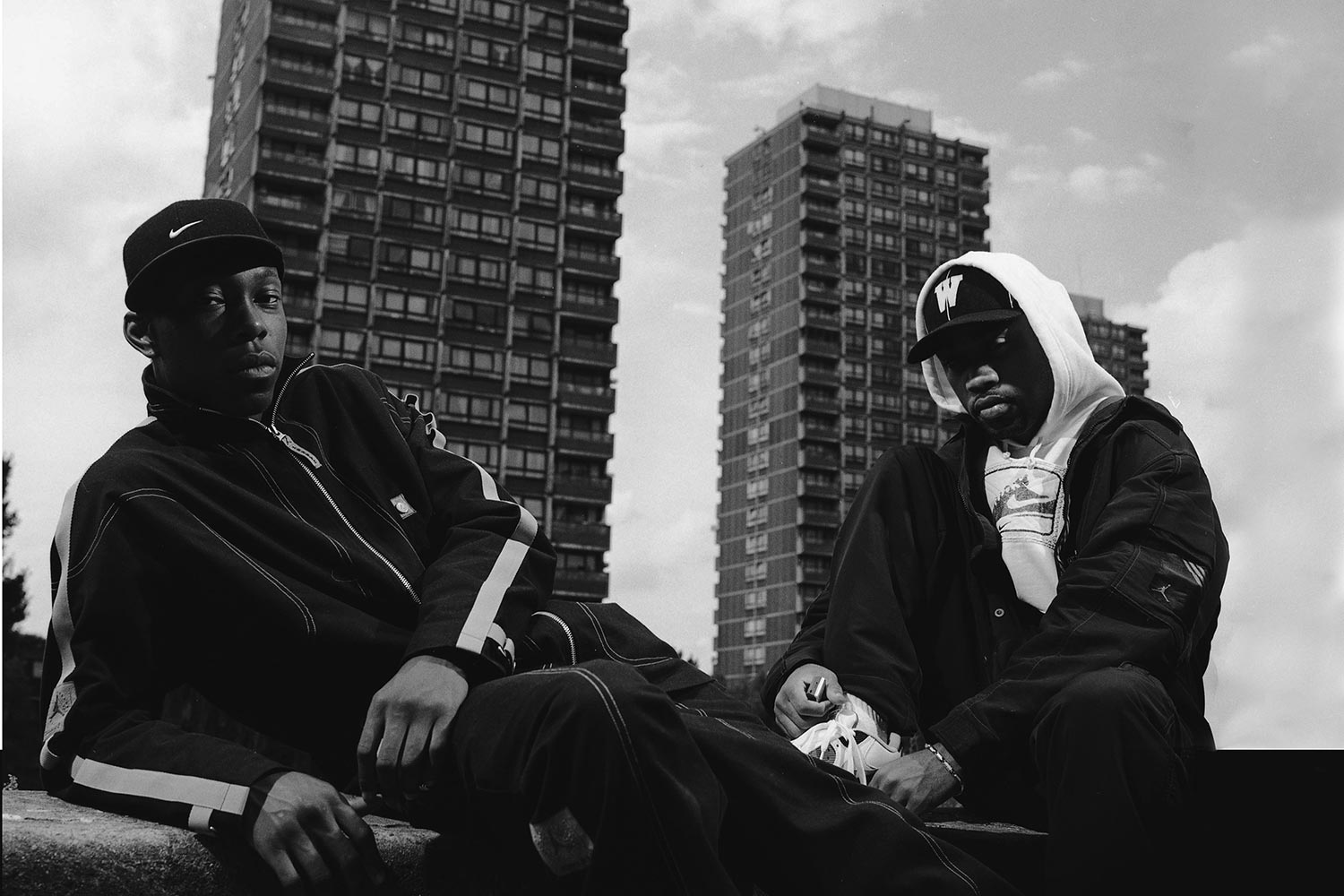 Wiley and Dizze, two grime artists, on a wall in front of three blocks of flats in East London, black and white photography