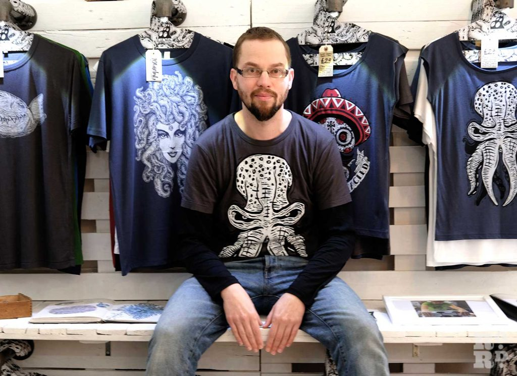Designer sits in front of his T shirt collection in Bamboo and Bee store