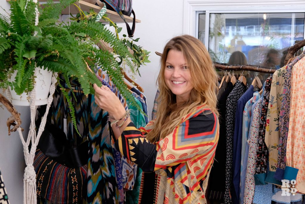 A designer stands by some of her brightly coloured and patterned clothes