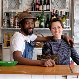 Co-owners of Muxima restaurant stand behind deli counter smiling
