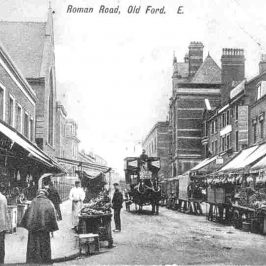 Image of Roman Road showing a horse and carriage, shops with awnings and market stalls
