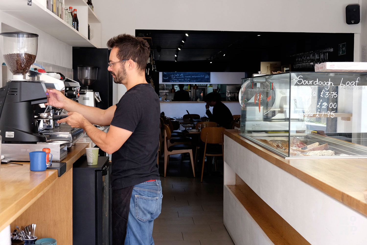 A barista behind a counter making coffee