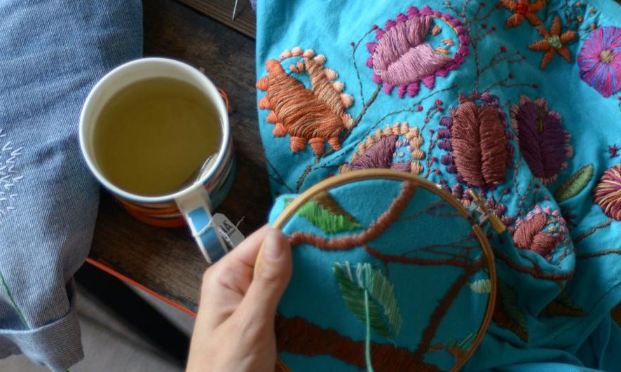 A hand holds embroidery frame next to a cup of tea