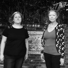 Two women stand in a garden