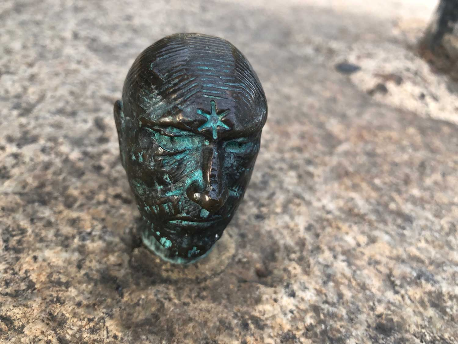 Small bronze sculpture of a man's head with a star on his forehead
