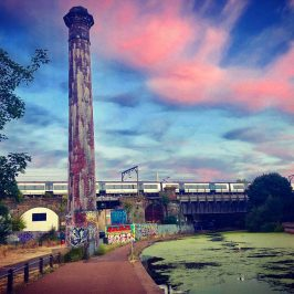 Brick tower by algae covered canal with dramatic sky